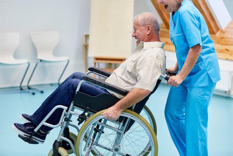 Anhörigvårdare albert med en pensionär i en rullstol arkivbilder