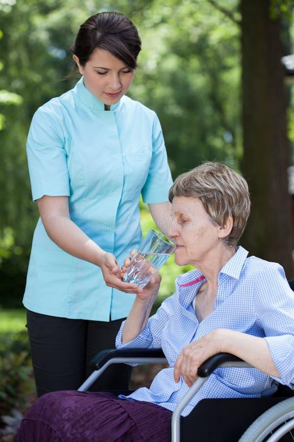 Anhörigvårdare som ger exponeringsglas av vatten till den höga kvinnan royaltyfri foto