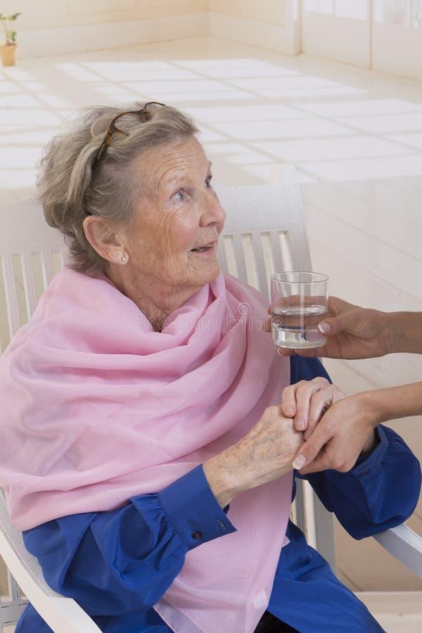 Anhörigvårdare som ger exponeringsglas av vatten till en elegant hög kvinna på nu royaltyfri fotografi