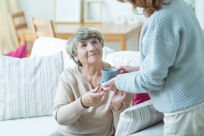 Anhörigvårdare som ger kaffe för äldre kvinna royaltyfri bild