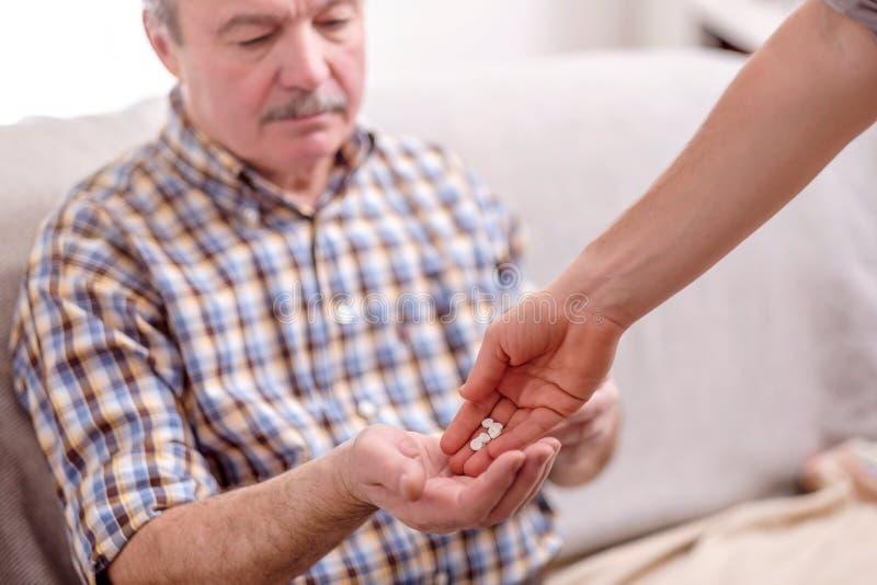 Anhörigvårdare som ger medicinen till äldre manlig patient arkivfoton