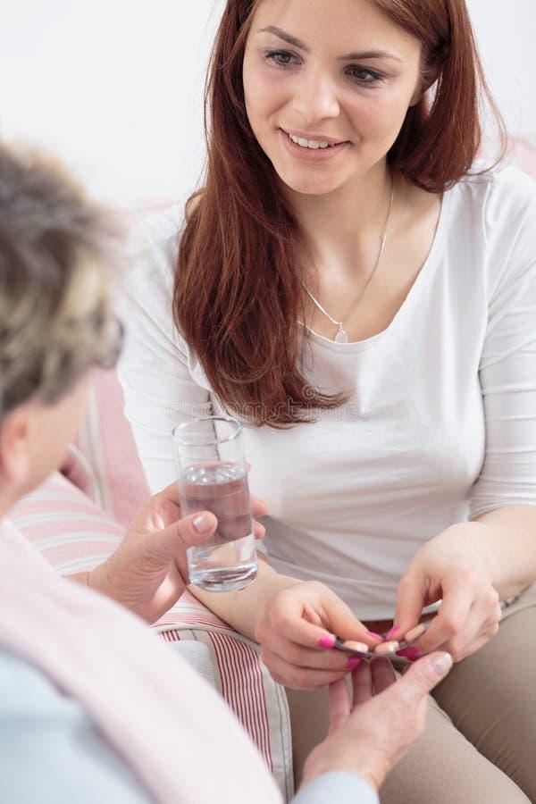 Anhörigvårdare som ger preventivpillerar till den äldre kvinnan med alzheimer i sjukvårdhuset royaltyfri bild