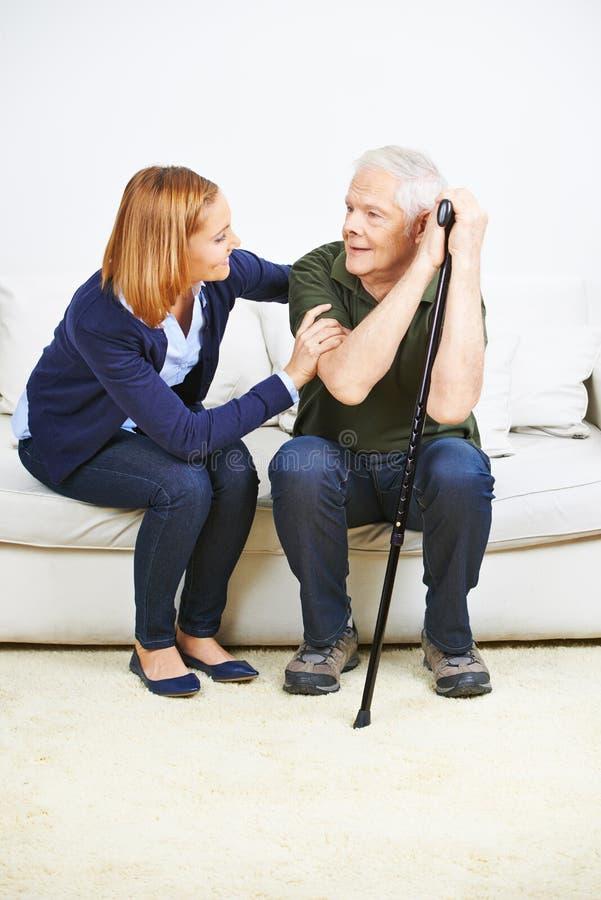 Anhörigvårdare som hemma talar till den höga mannen royaltyfria foton
