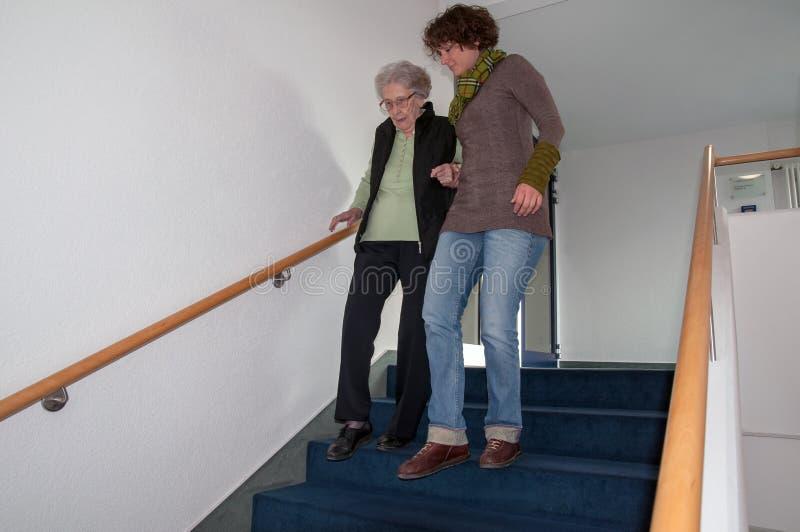 Anhörigvårdare som hjälper den höga kvinnan som går ner trappan arkivfoton