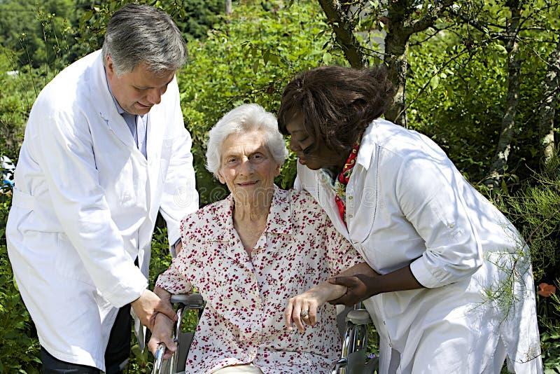 Anhörigvårdare som hjälper en hög patient i rullstol fotografering för bildbyråer