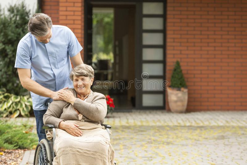 Anh?rigv?rdare som hj?lper le den r?relsehindrade h?ga kvinnan i rullstolen framme av huset arkivfoto