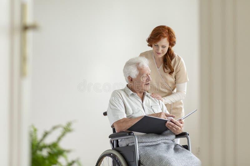 Anhörigvårdare som stöttar den lamma äldre mannen i en rullstol med royaltyfria foton