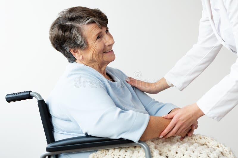Anhörigvårdare som stöttar den rörelsehindrade höga kvinnan i en rullstol arkivfoton