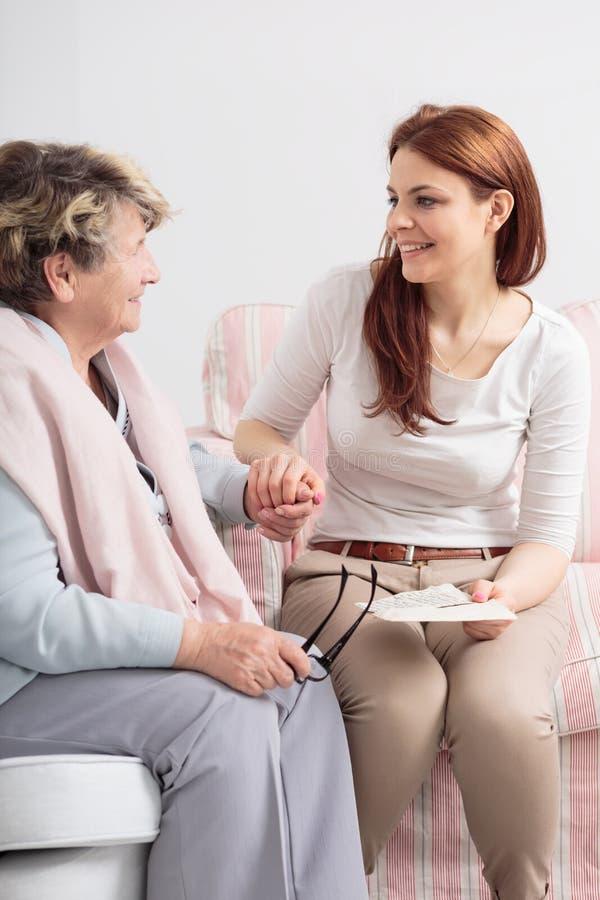 Anhörigvårdare som talar med att le den höga kvinnan medan besök henne på att vårda huset royaltyfri bild