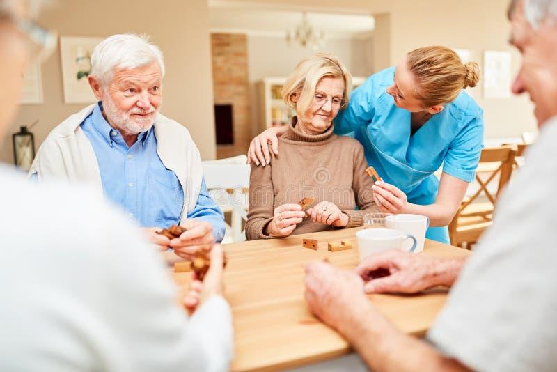 Anhörigvårdaren att bry sig för en hög kvinna med demens arkivbild