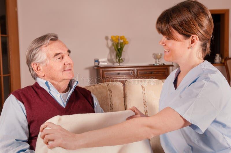 Anhörigvårdaren ger filten till den lyckliga pensionären fotografering för bildbyråer