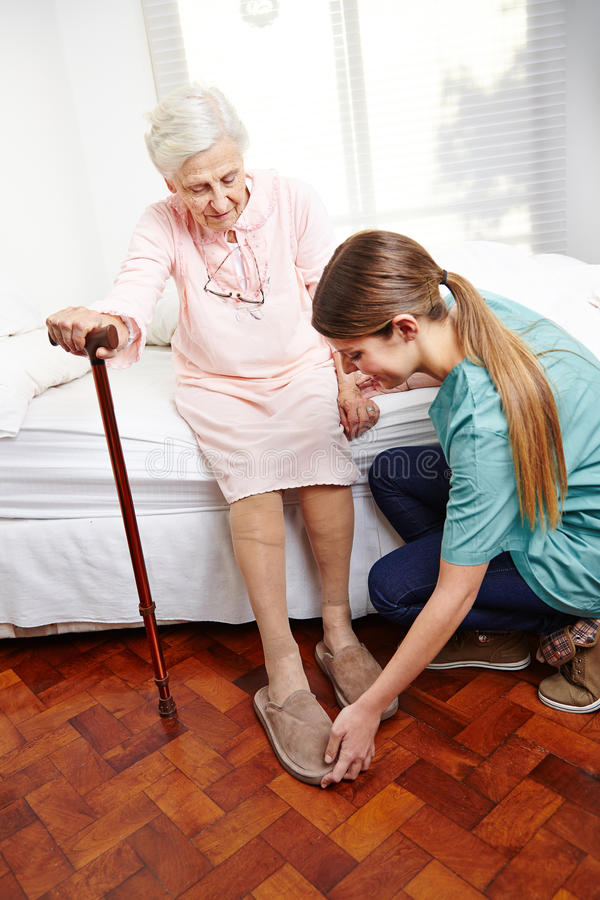 Anhörigvårdaren hjälper att klä pensionären royaltyfria foton