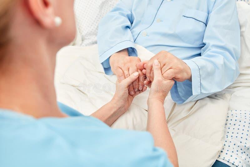 Anhörigvårdaren rymmer händerna av en sjuk pensionär royaltyfri bild