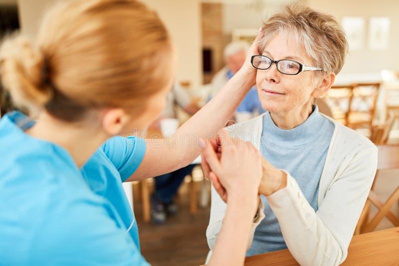 Anhörigvårdaren tröstar pensionärer med demens royaltyfria bilder