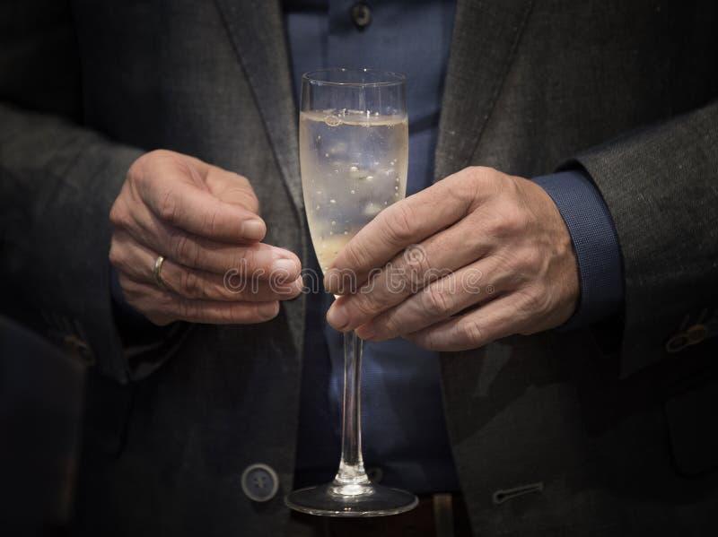 Anhalten eines Glases von Champagne stockfotos