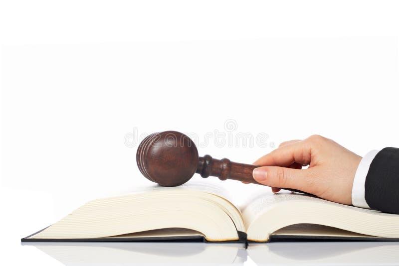 Anhalten eines hölzernen Hammers über dem Gesetzbuch stockbilder