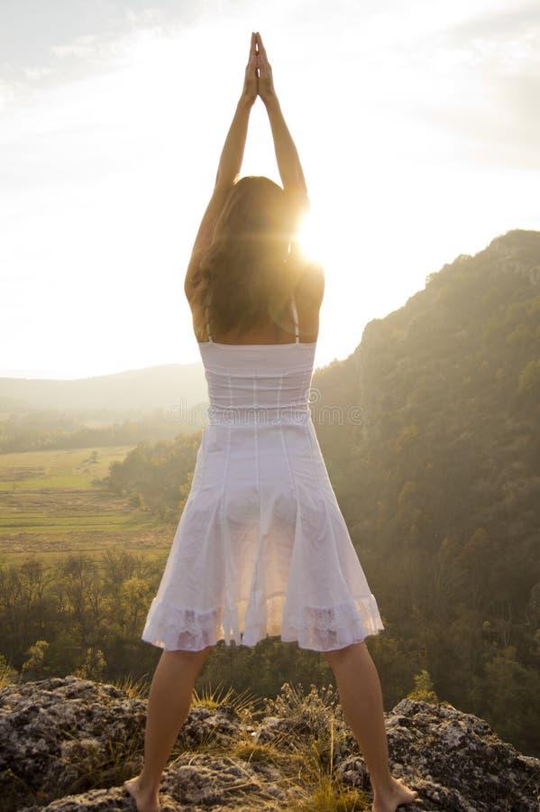 Anheben der Arme, um die Sonne zu grüßen stockfotos