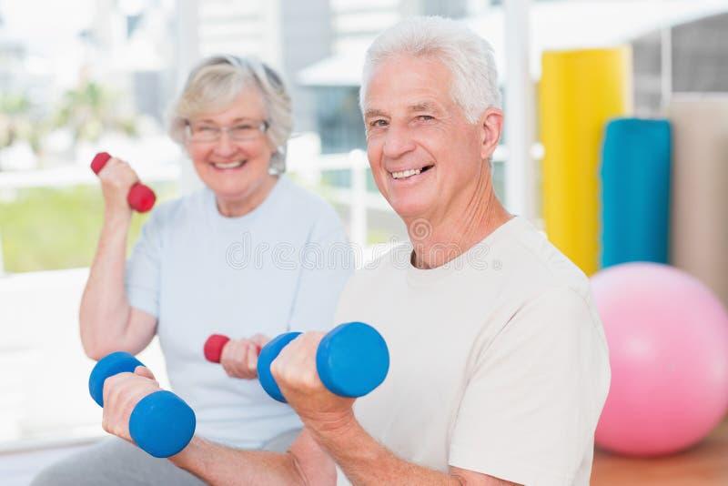 Anhebende Dummköpfe der glücklichen älteren Paare in der Turnhalle lizenzfreie stockfotos
