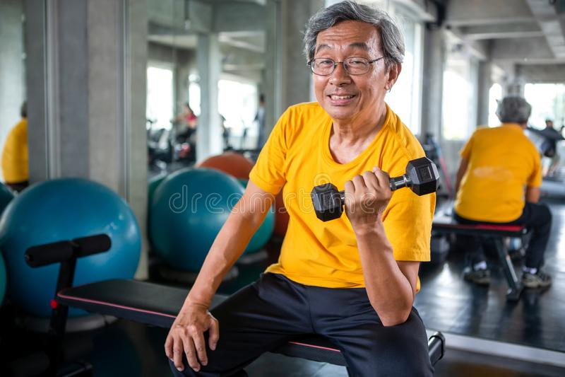 Anhebende Dummköpfe des älteren asiatischen Sportmannes in der Eignungsturnhalle älterer Mann, der, arbeitend, Ausbildungsgewicht stockbilder