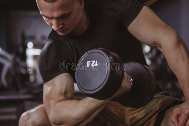 Anhebende Dummköpfe des männlichen Bodybuilders an der Turnhalle stockfotos