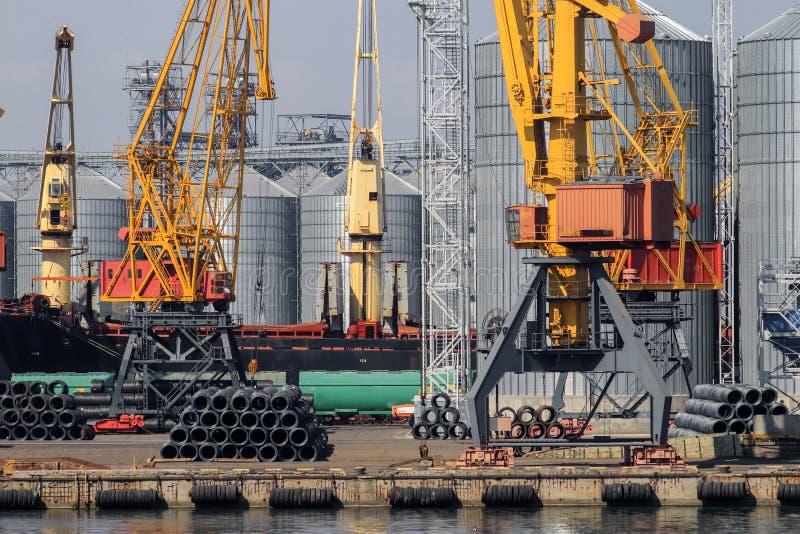 Anhebende Frachtkräne, Schiffe und Korntrockner im Meer Por stockbild
