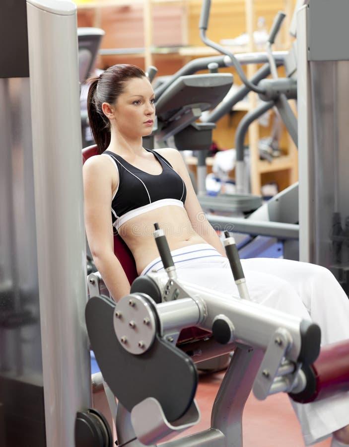 Anhebende Gewichte der attraktiven Frau mit einer Fahrwerkbeinpresse lizenzfreies stockfoto