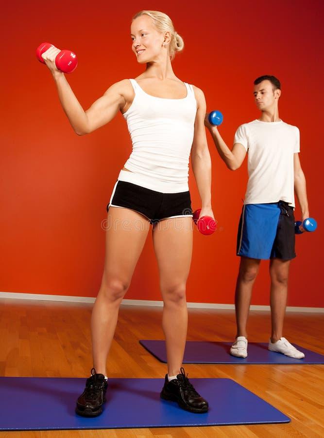 Anhebende Gewichte der Gruppe von Personen in der Gymnastik stockbilder