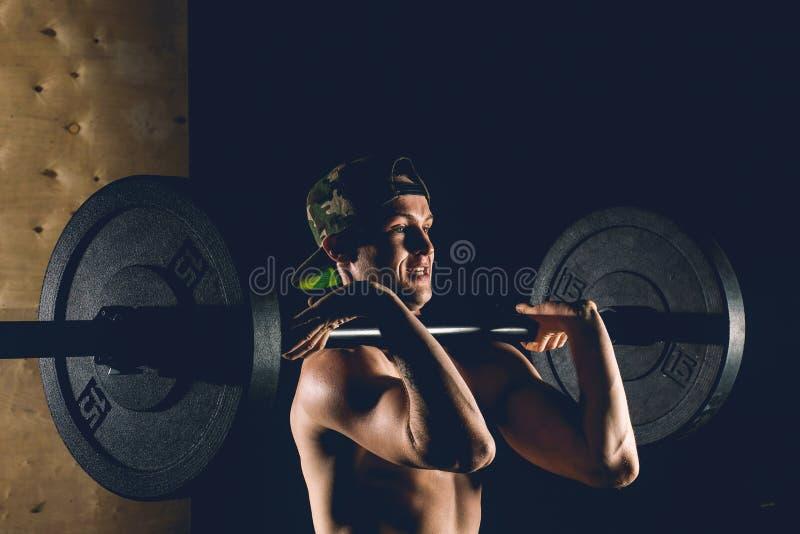 Anhebende Gewichte des Mannes Muskulöses Manntraining in der Turnhalle, die Übungen mit Barbell tut lizenzfreies stockbild