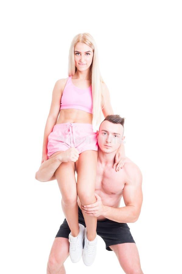 Anhebendes Eignungsmädchen des starken Bodybuilders auf seiner Schulter stockfotografie