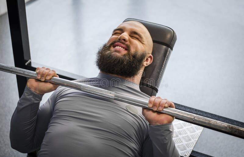 Anhebendes Gewicht des starken Mannes in der Turnhalle, männliches Athletentraining am Fitness-Club stockbilder