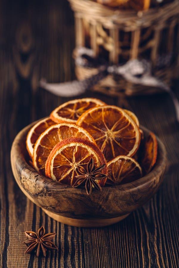 Anijsplant en droge sinaasappelen in kom op een houten lijst stock afbeeldingen