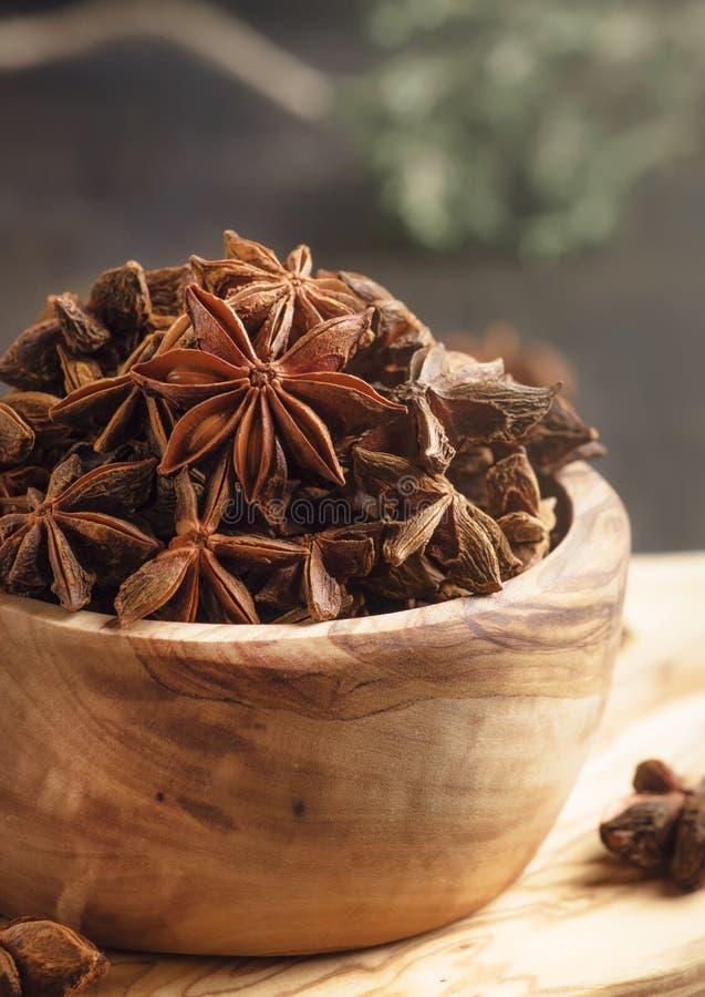 Anijsplantsterren in houten kom, de donkere achtergrond van de keukenlijst, selectieve nadruk royalty-vrije stock afbeeldingen