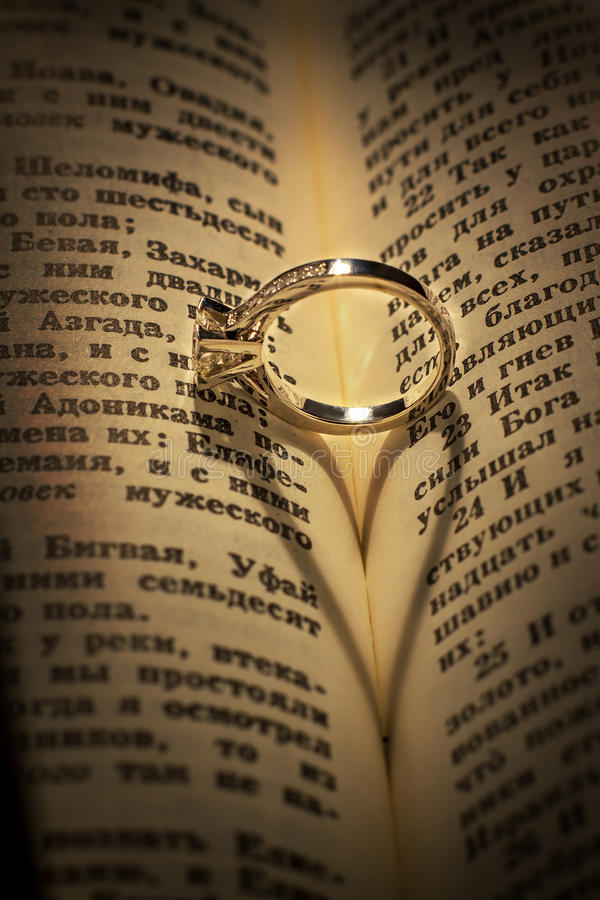 Anillo de bodas del oro en una biblia imagenes de archivo