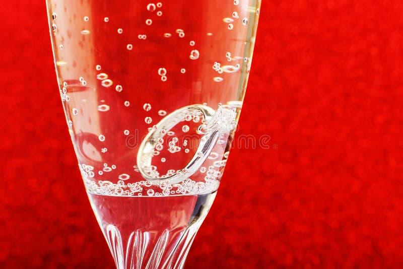 Anillo de bodas de diamante del oro blanco con platino en un vidrio del champán Boda, oferta como regalo para día de San Valentín foto de archivo