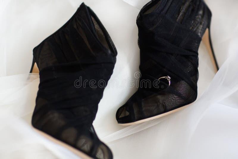 Anillo de bodas en los zapatos que se casan negros en el fondo blanco fotografía de archivo