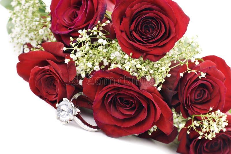Anillo de compromiso con las rosas rojas imagen de archivo