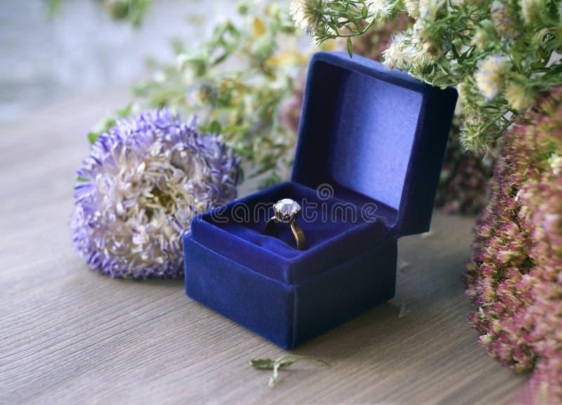 Anillo de compromiso del diamante del oro del vintage en caja azul del terciopelo fotos de archivo