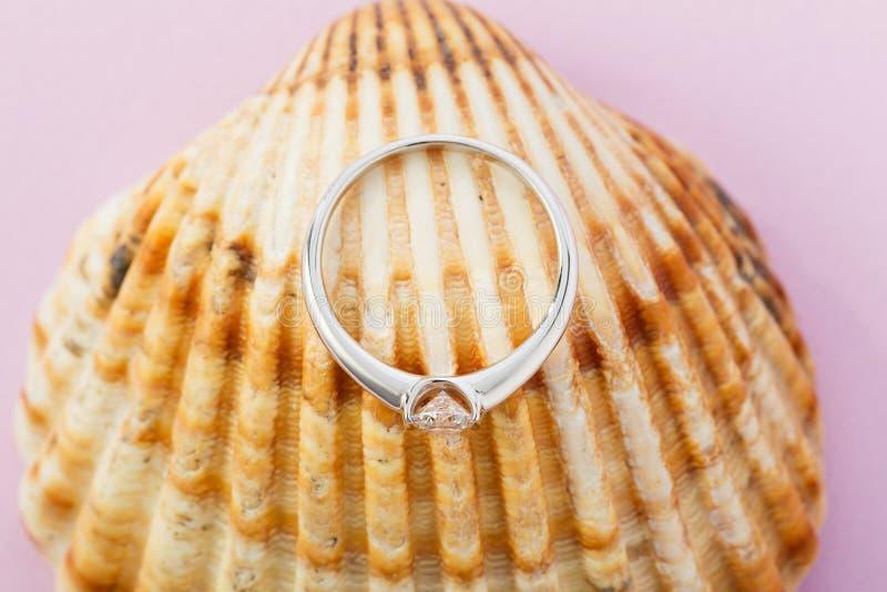 Anillo de compromiso del oro blanco con el diamante en fondo de la concha marina foto de archivo libre de regalías