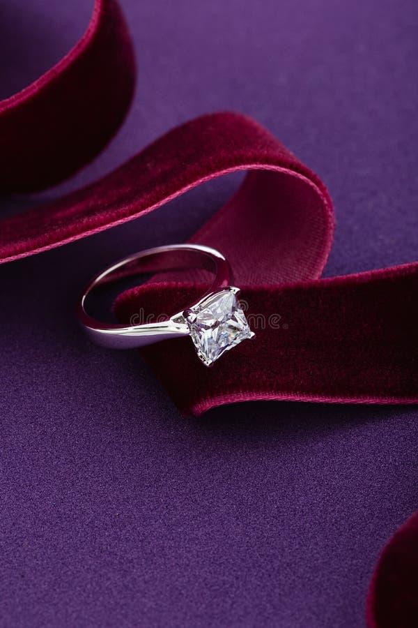 Anillo de compromiso del oro blanco con el diamante grande en fondo púrpura imagen de archivo libre de regalías