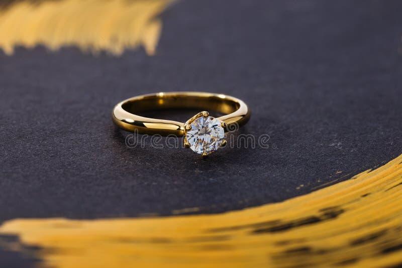 Anillo de compromiso del oro con el diamante en fondo negro imagen de archivo