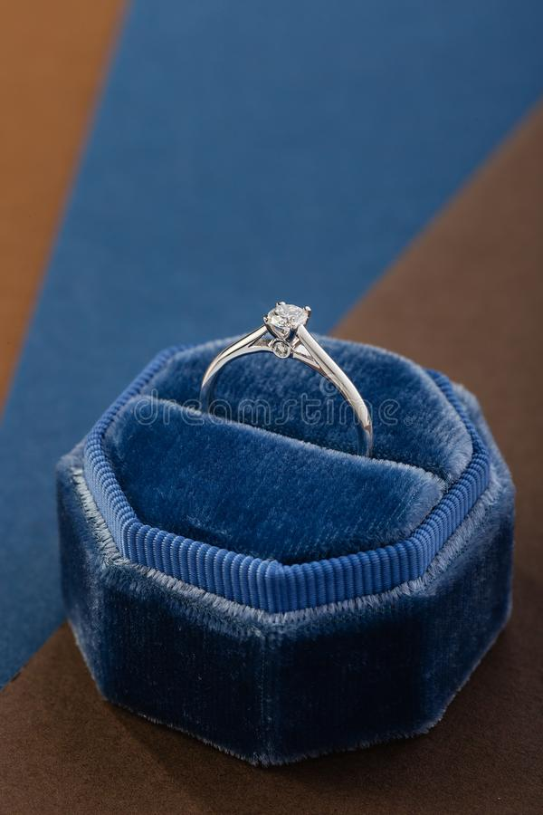 Anillo de compromiso de oro blanco con el diamante en caja azul del anillo del terciopelo del vintage imagen de archivo libre de regalías