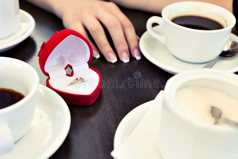 Anillo de compromiso y café foto de archivo