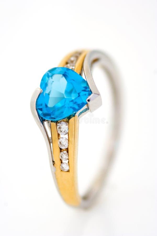Anillo de diamantes del oro con el zafiro azul en forma de corazón imagenes de archivo
