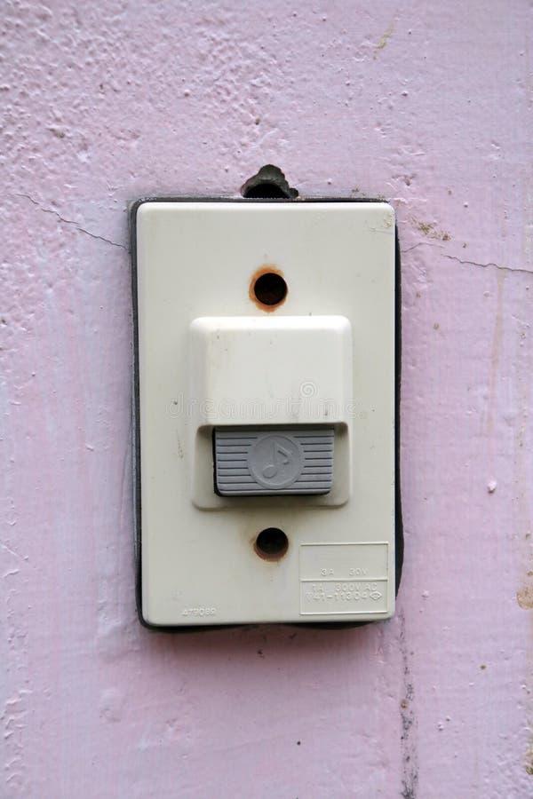 Anillo de la campana de puerta en la pared rosada el timbre es una campana en un edificio que se pueda sonar por los visitantes imagenes de archivo