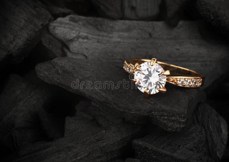Anillo de la joyería con el diamante grande en el fondo oscuro del carbón, foc suave fotos de archivo
