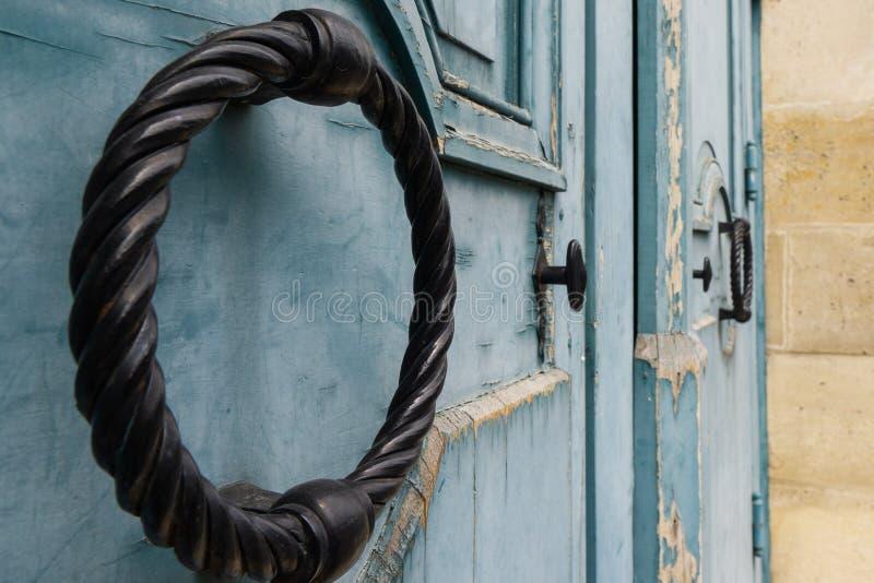 Anillo de mimbre de la puerta del metal negro El anillo en el azul de madera viejo de la puerta foto de archivo libre de regalías