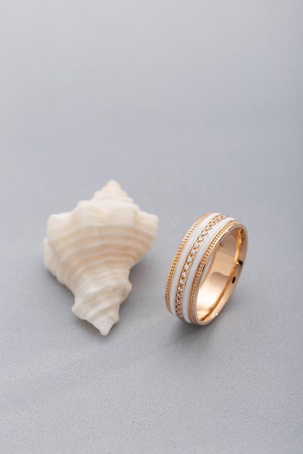 Anillo de oro con el esmalte blanco y diamantes en fondo gris con la concha marina imagen de archivo libre de regalías