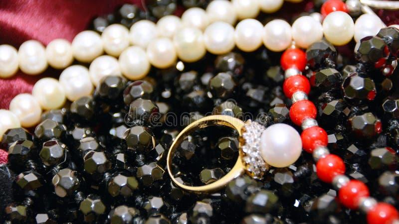 Anillo de oro con la perla y la circona cúbica, en un collar negro y gotas del coral rojo de las perlas del blanco fotos de archivo libres de regalías