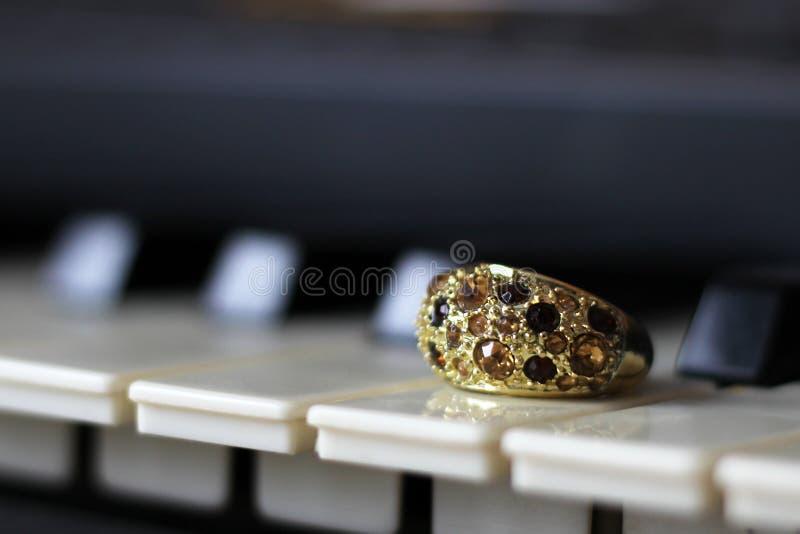 Anillo de oro con las piedras en el piano fotografía de archivo libre de regalías