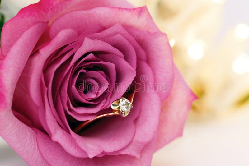 Anillo de oro de la boda con el diamante y las flores color de rosa imagenes de archivo